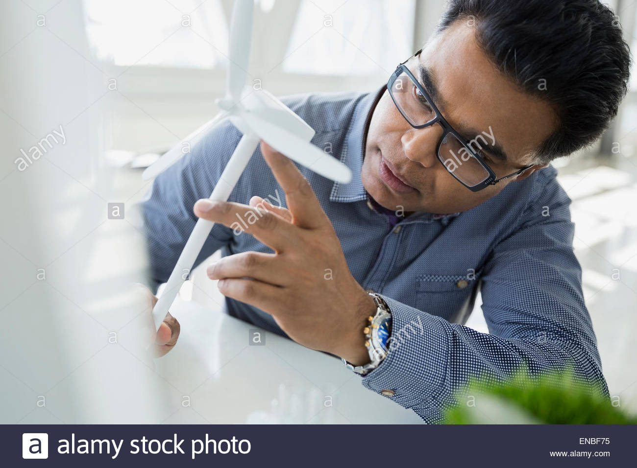 Serious scientist examining wind turbine model - Stock Image