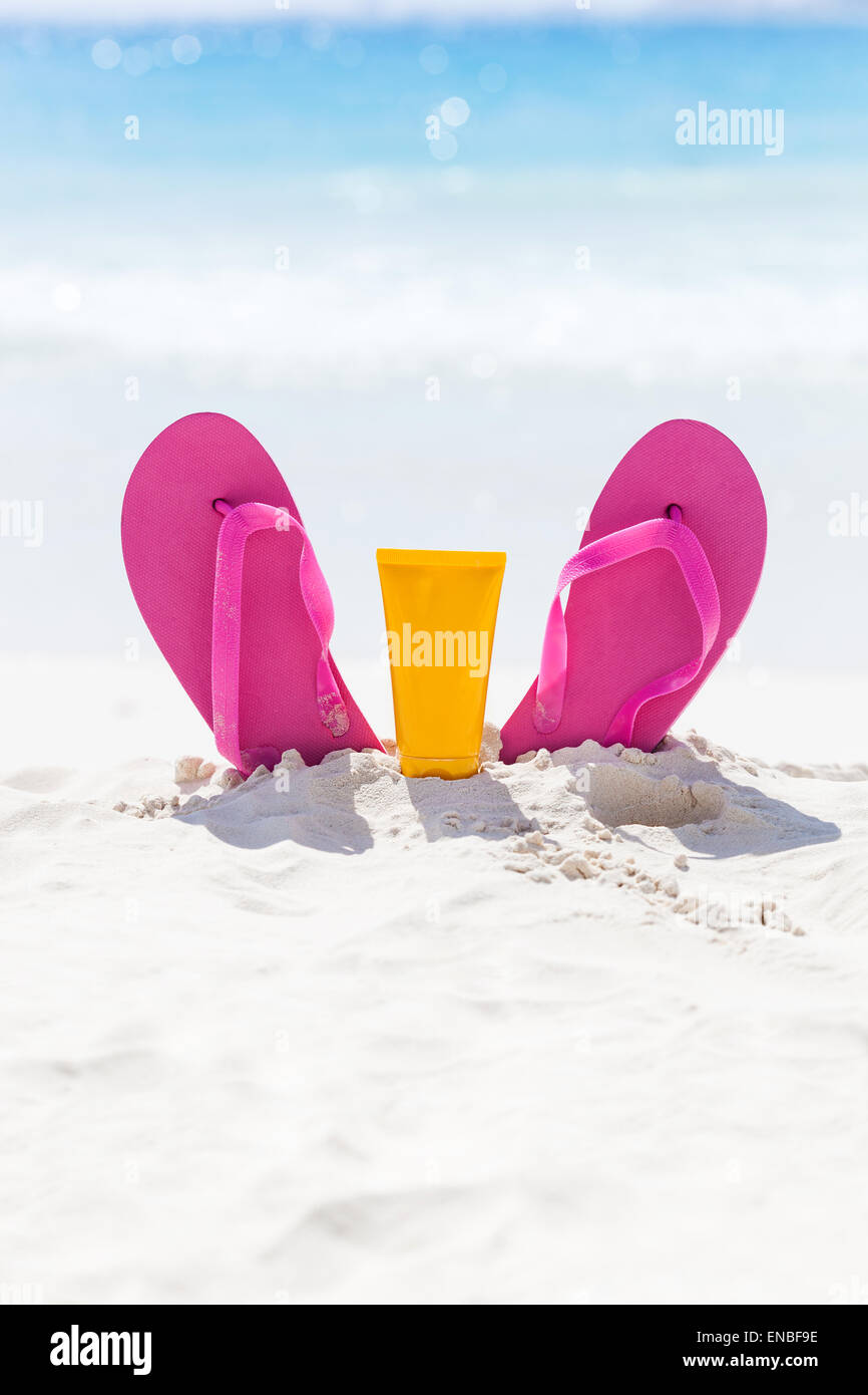 7296321bcfd8f Pink vibrant beach flip flops with sunscreen protection face cream in white  sand on sea background