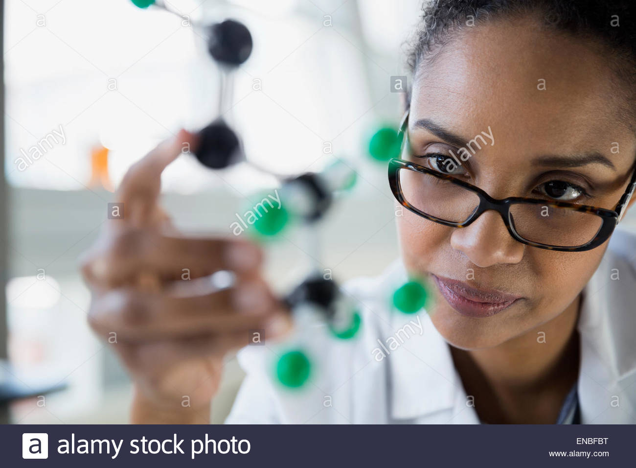 Focused scientist examining atom model - Stock Image