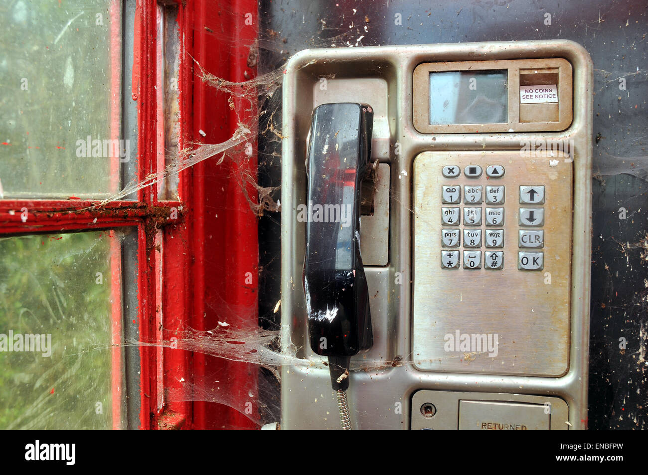 Spiders web across  a handset in an old telephone  kiosk - Stock Image