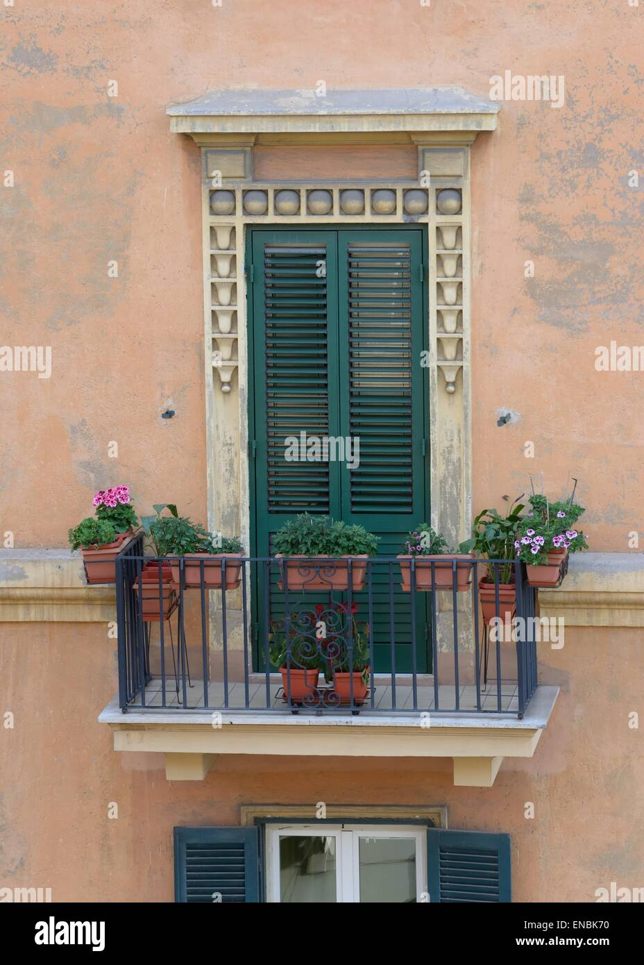 Italian style balcony with boxes of flowers and louvered door - Stock Image