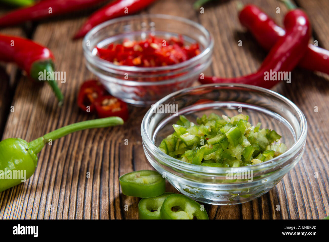 Red and Green Chilis (cutted) on wooden background - Stock Image