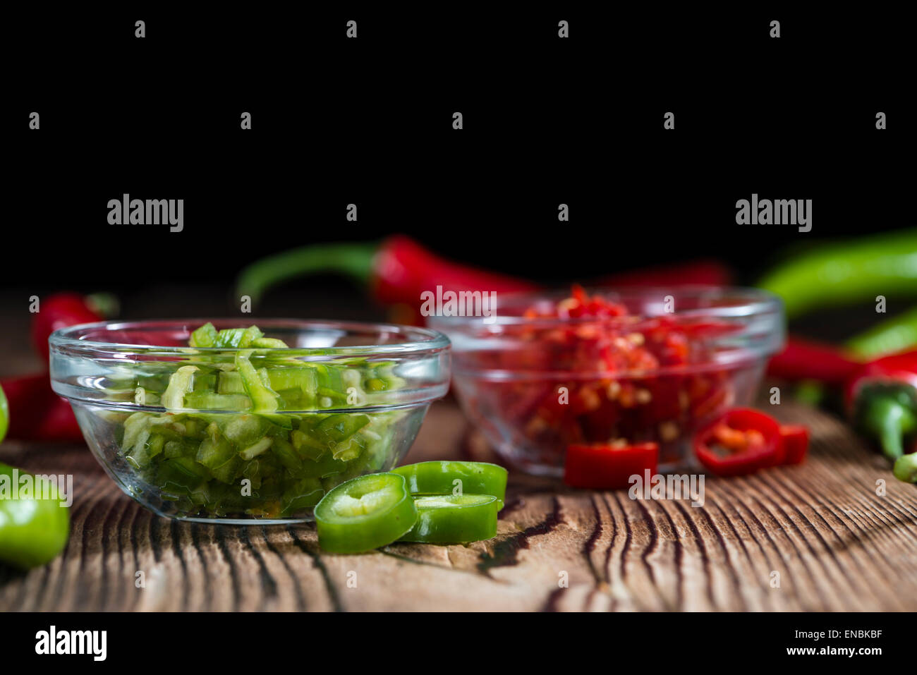 Mixed cutted Chilis (red and green) on vintage wooden background - Stock Image