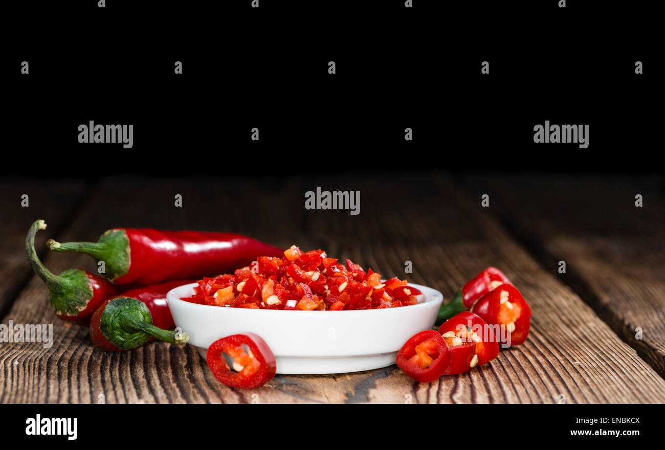 Red Chilis (cutted) on vintage wooden background - Stock Image