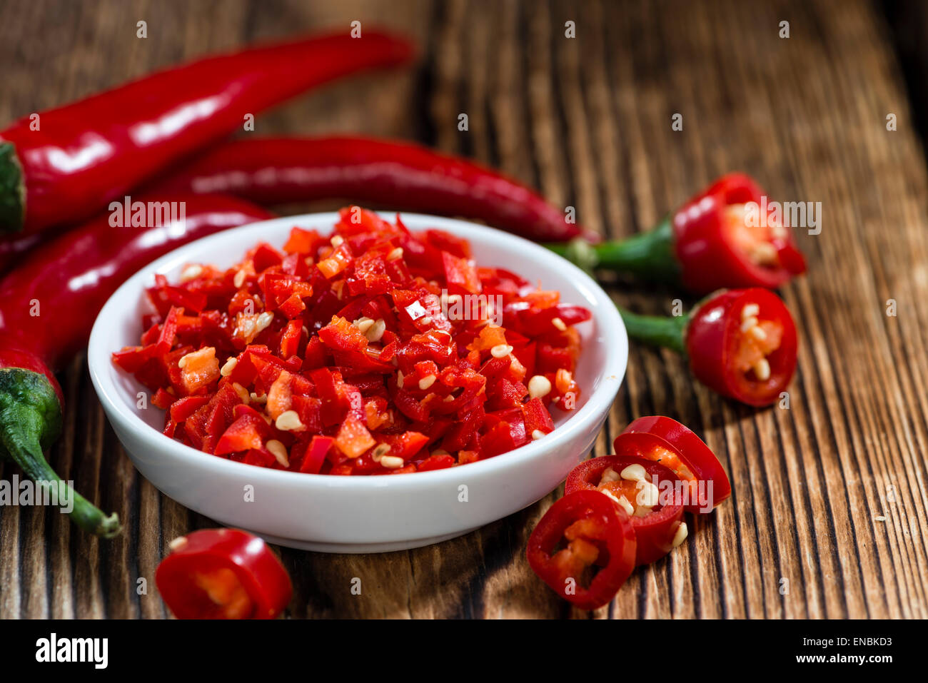 Cutted red Chilis (close-up shot) on wooden background - Stock Image