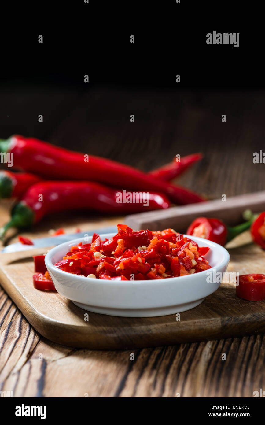 Cutted red Chilis in a bowl (close-up shot) on wooden background - Stock Image