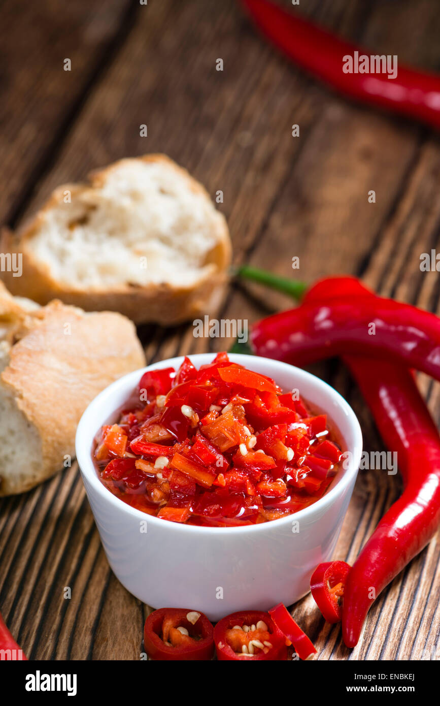 Small bowl with preserved red Chilis (on wooden background) - Stock Image
