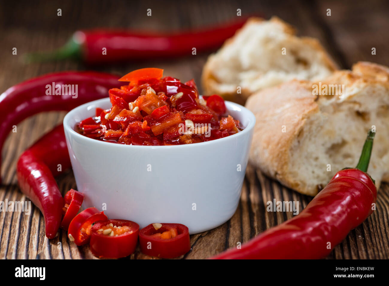 Preserved red Chilis (close-up shot) on wooden background - Stock Image