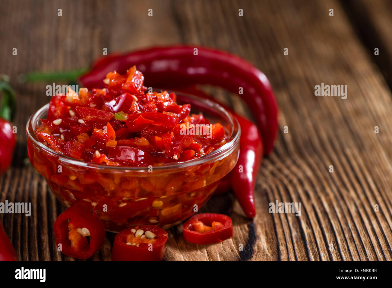 Homemade Chili Dip (preserved with olive oil) on wooden background - Stock Image