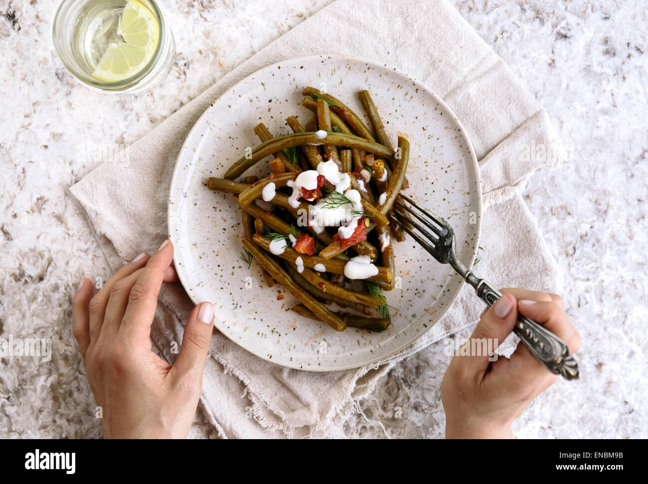 Mediterranean-Style Green Beans served on a plate and a person is about to eat it. - Stock Image