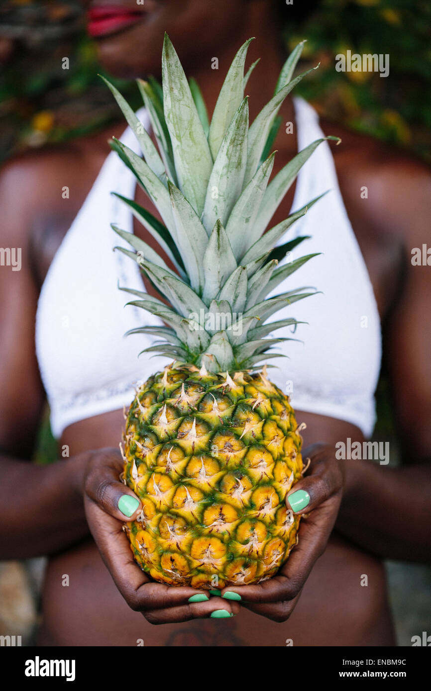 A Caribbean woman holding a fresh pineapple in her hand. - Stock Image