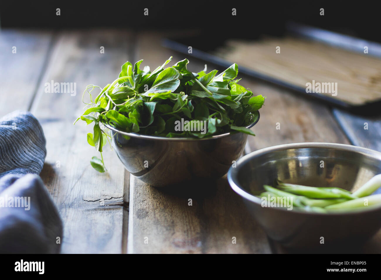 Pea shoots in a metallic bowl - Stock Image