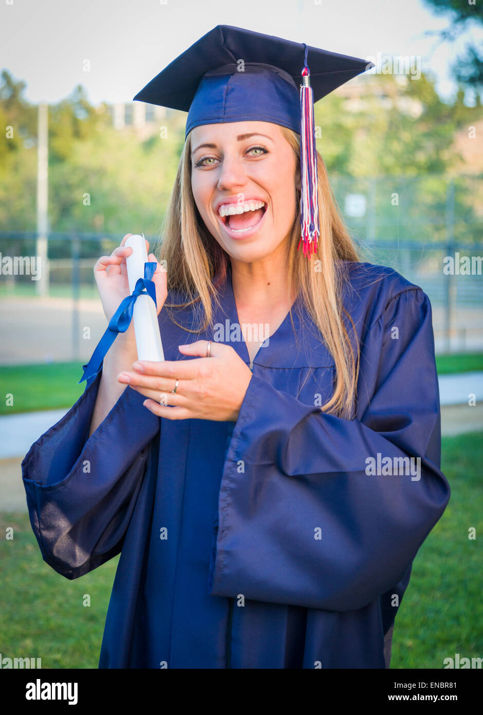 Excited and Expressive Young Woman Holding Diploma in Cap and Gown Outdoors. - Stock Image