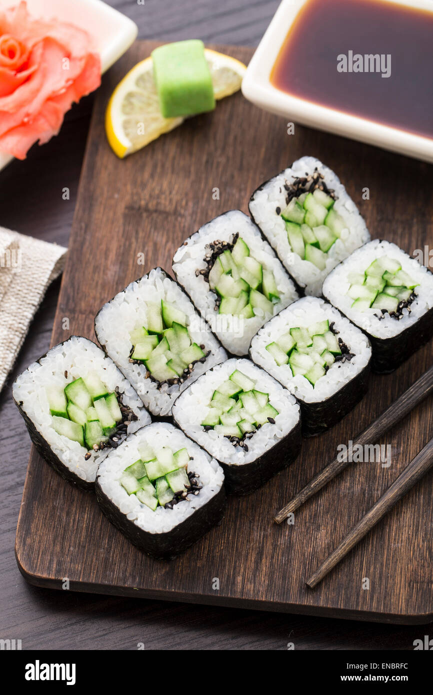 Sushi rolls with cucumber and sesame seed on a wooden board - Stock Image