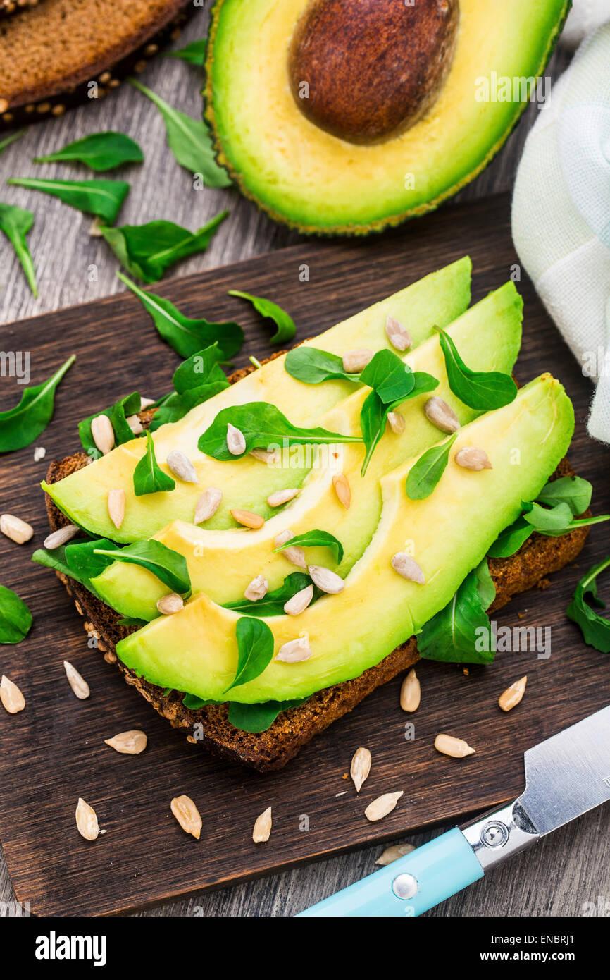 Avocado sandwich with arugula and sunflower seeds - Stock Image