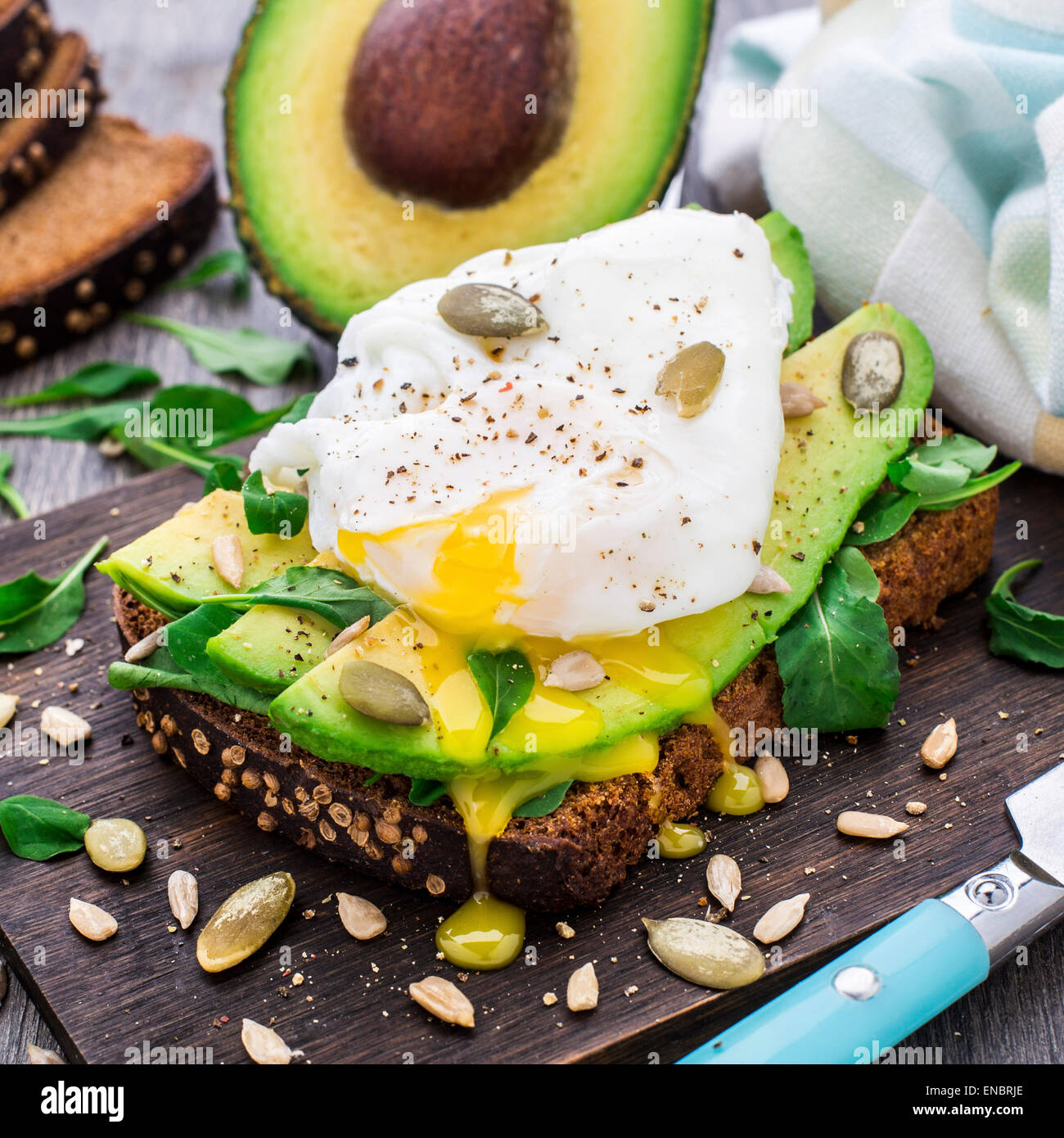 Avocado sandwich with arugula, seeds and poached egg - Stock Image