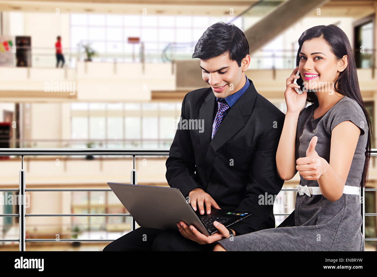 2 indian Business Colleague Mall laptop and phone working - Stock Image
