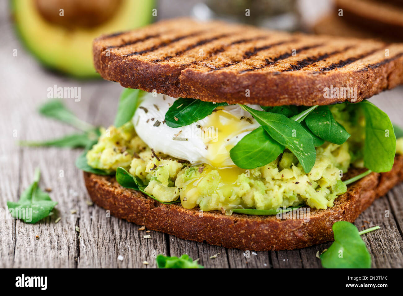 Grilled sandwich with avocado, poached egg and arugula on wooden table - Stock Image