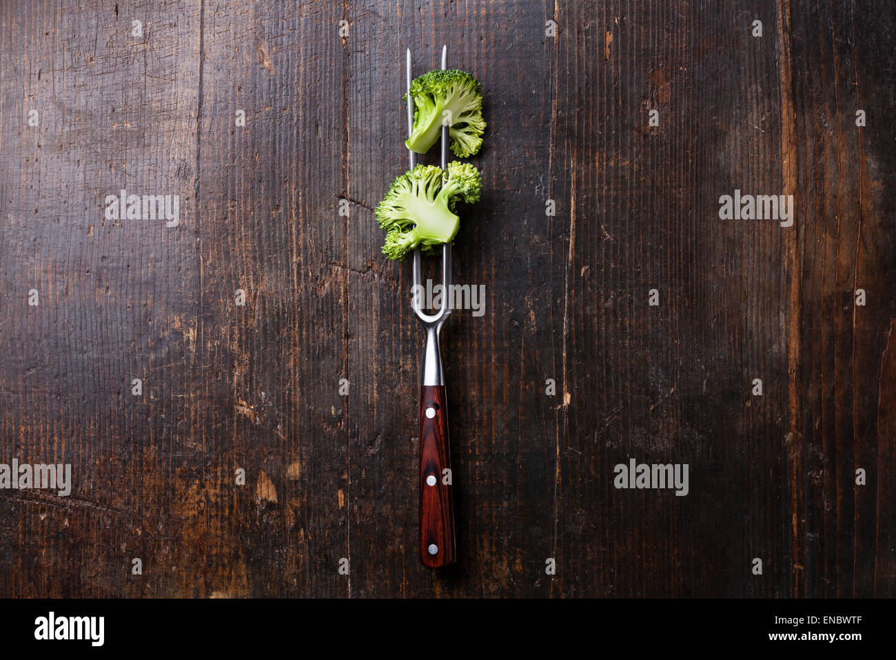 Fresh broccoli on meat fork on dark wooden background - Stock Image