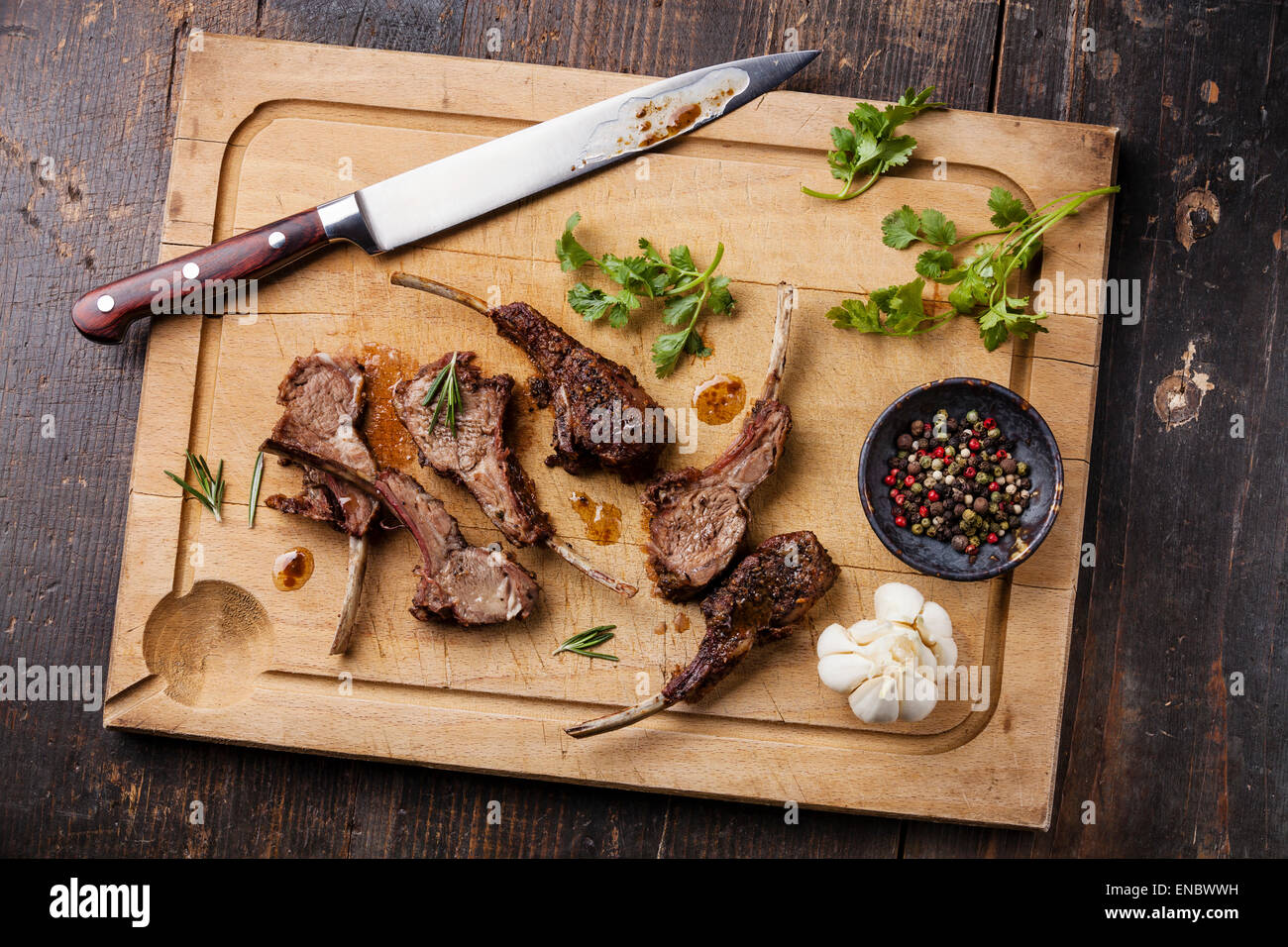 Roasted lamb ribs and kitchen knife on wooden cutting board on dark background - Stock Image