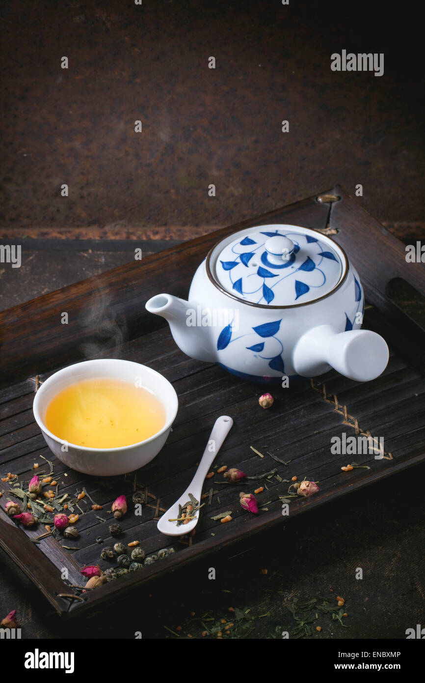 Traditional japanese teapot and cup of green tea, served on bamboo tray with dry tea variations over dark background - Stock Image