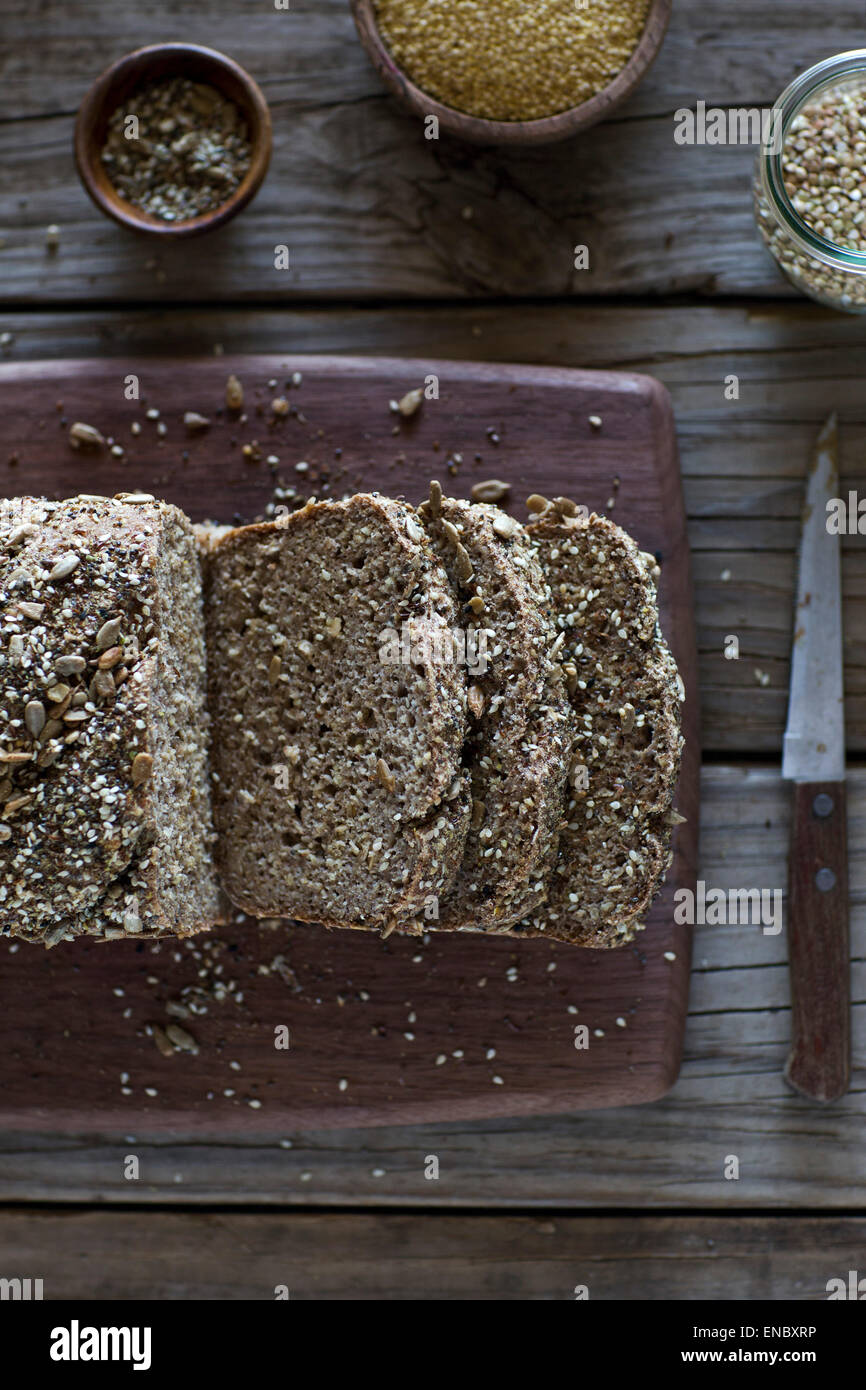 Freshly Baked Millet and Buckwheat Bread sliced on a cutting board. - Stock Image