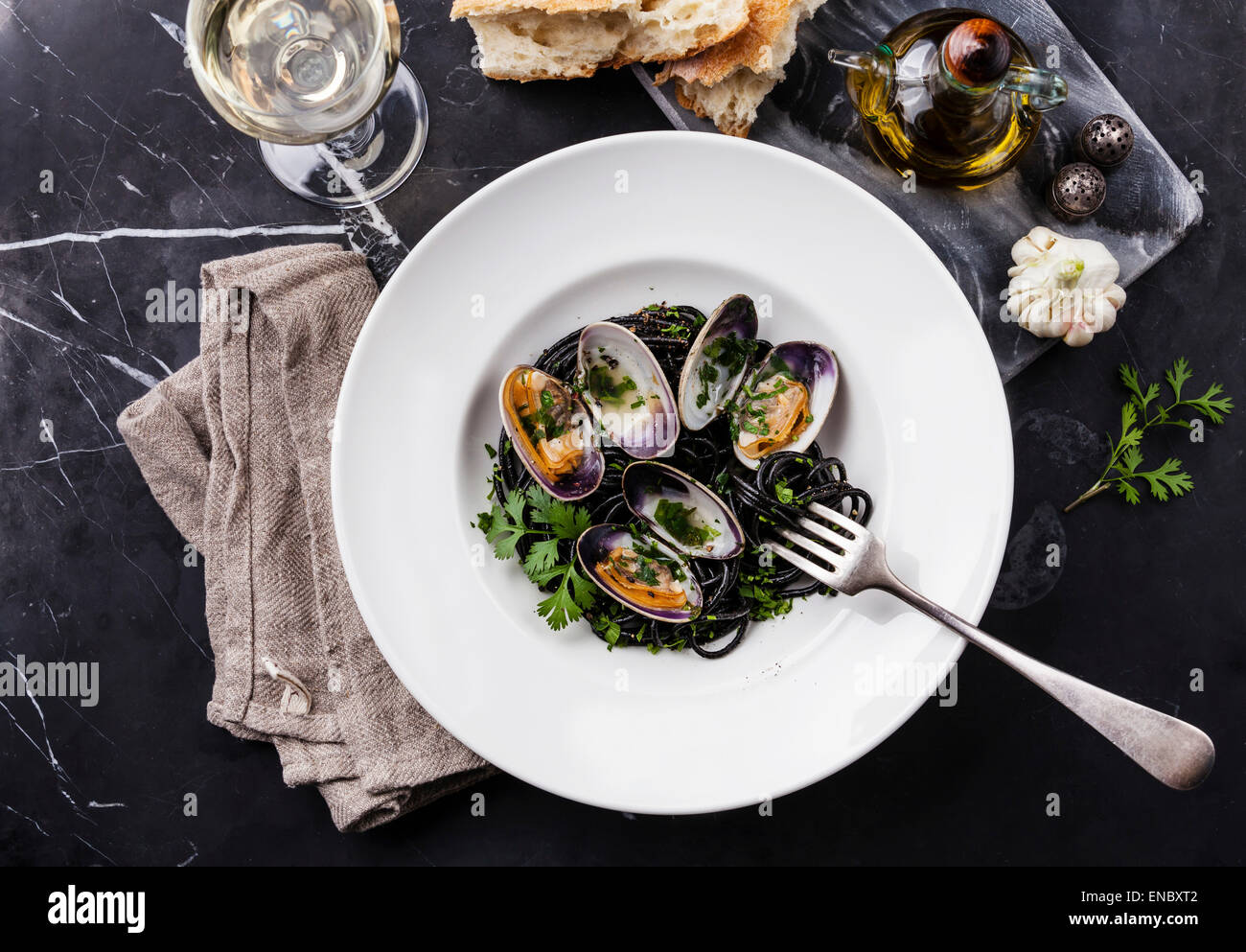 Seafood pasta with clams Spaghetti Vongole on white plate on dark marble background - Stock Image