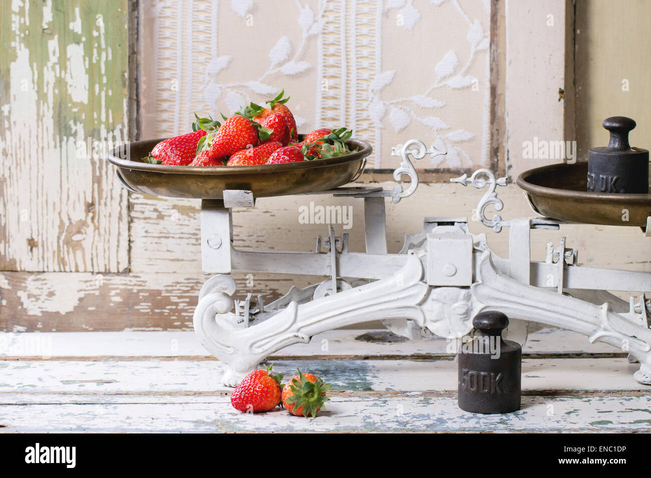 Weights and vintage scales with fresh strawberries over white wooden table - Stock Image