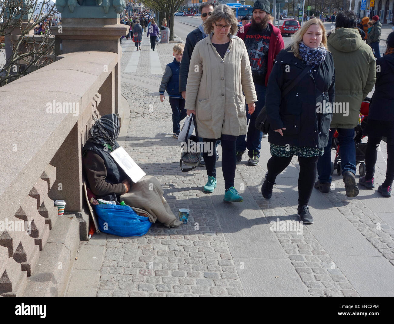 Middle aged Roma woman begs for alms on the busy Kungsportsbrun bridge, Gothenburg, Sweden Stock Photo