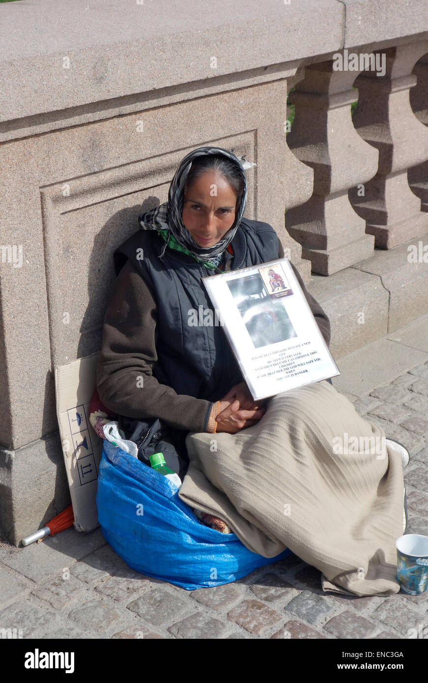 Middle aged Roma woman begs for alms on the Kungsportsbrun bridge, Gothenburg, Sweden Stock Photo