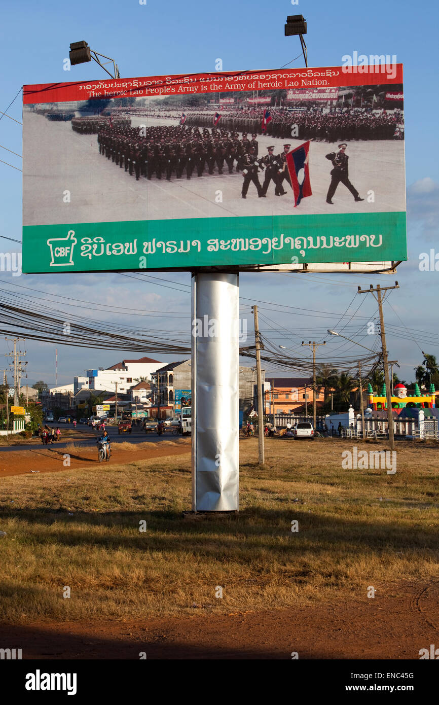 A poster in Pakse shows a military parade with the caption, ' the heroic Lao People's Army is the Army of - Stock Image