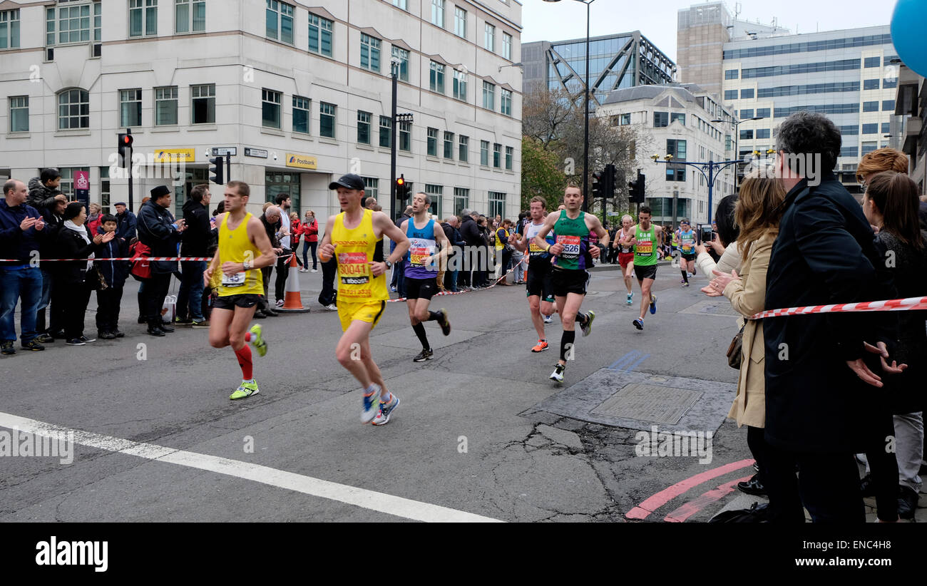 Competitors running in the 2015 London Marathon at the 38.5 km mark in Upper Thames Street London UK KATHY DEWITT - Stock Image