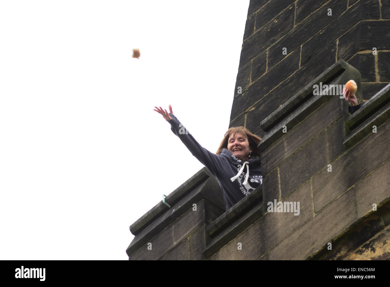 Rotherham, UK. 2nd May 2015. A church member throws a piece of bread from the church tower at Wath All Saints Parish Church near Rotherham, South Yorkshire. One hundred bread bun are thrown to the waiting crowds below as part of the annual Wath Festival. Picture: Scott Bairstow/ Alamy Stock Photo