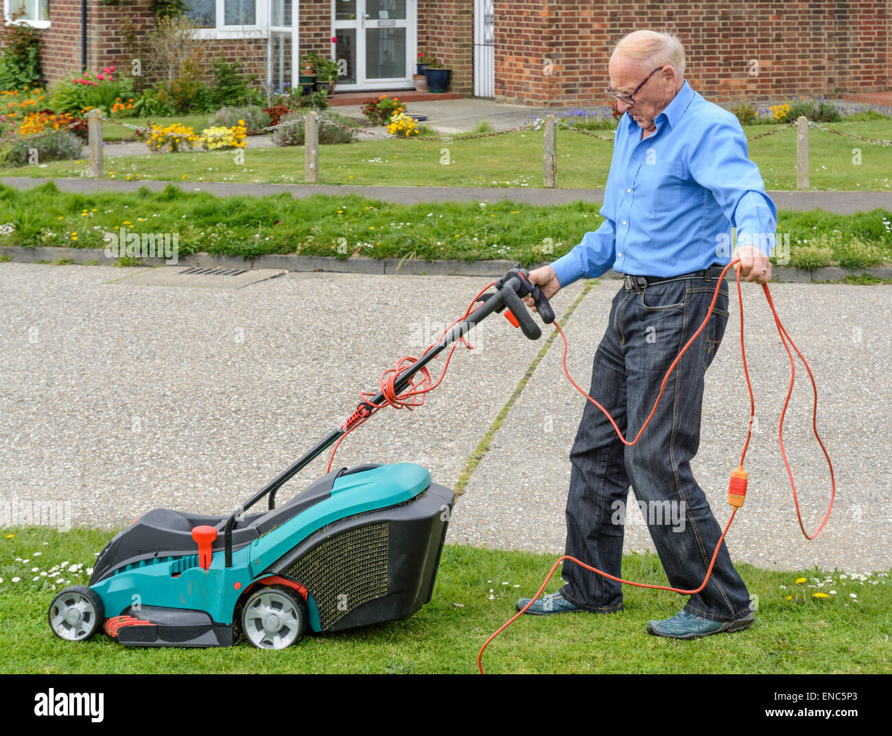 Elderly man mowing the grass verge by the roadside. - Stock Image