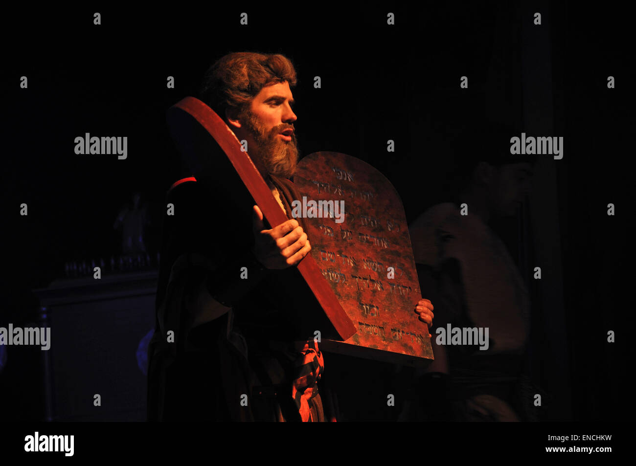 Actor dressed as Moses holding stage props of the Biblical Ten Commandments - Stock Image