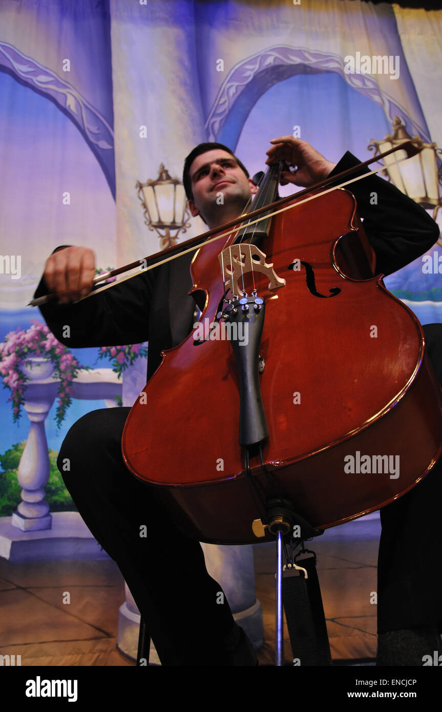 Mature man in formal dinner costume playing the cello in