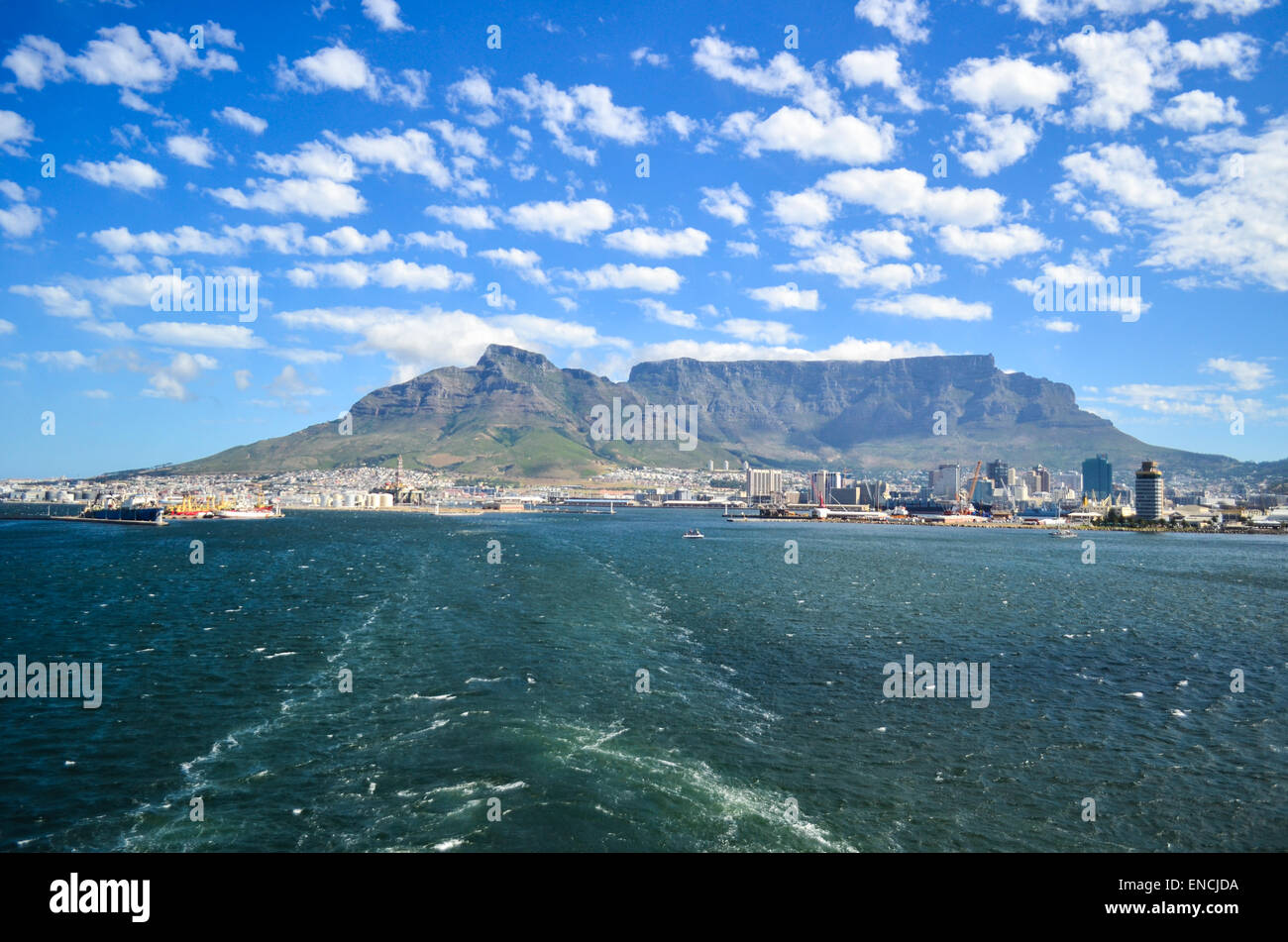 Trace of a cargo vessel in the sea, leaving the port of Cape Town, South Africa, and Table Mountain in the background - Stock Image