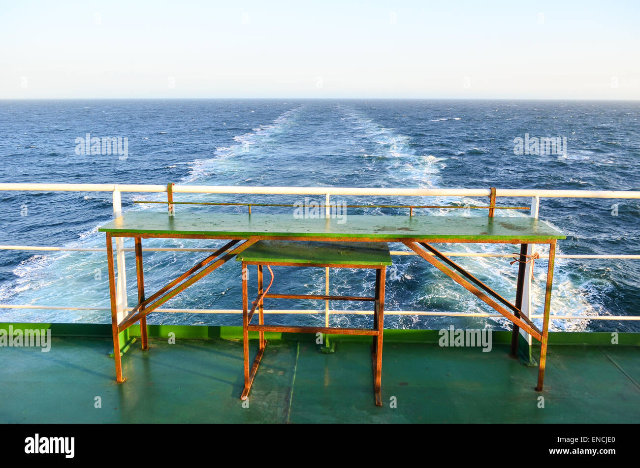 Freighter travel: empty table and trace of cargo ship in the open sea of the Atlantic ocean - Stock Image