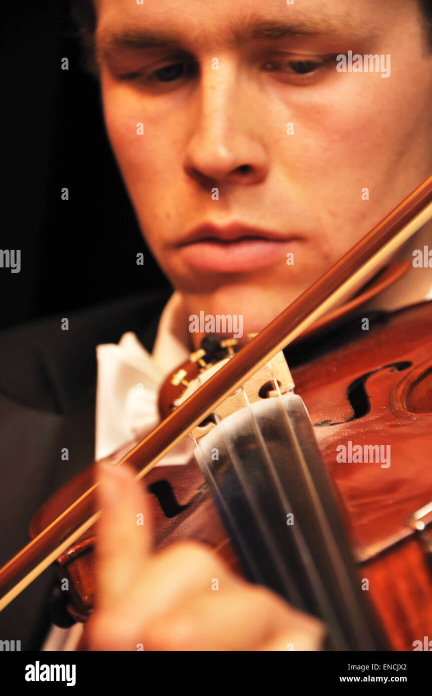 Detail of a man playing a violin in a live performance - Stock Image