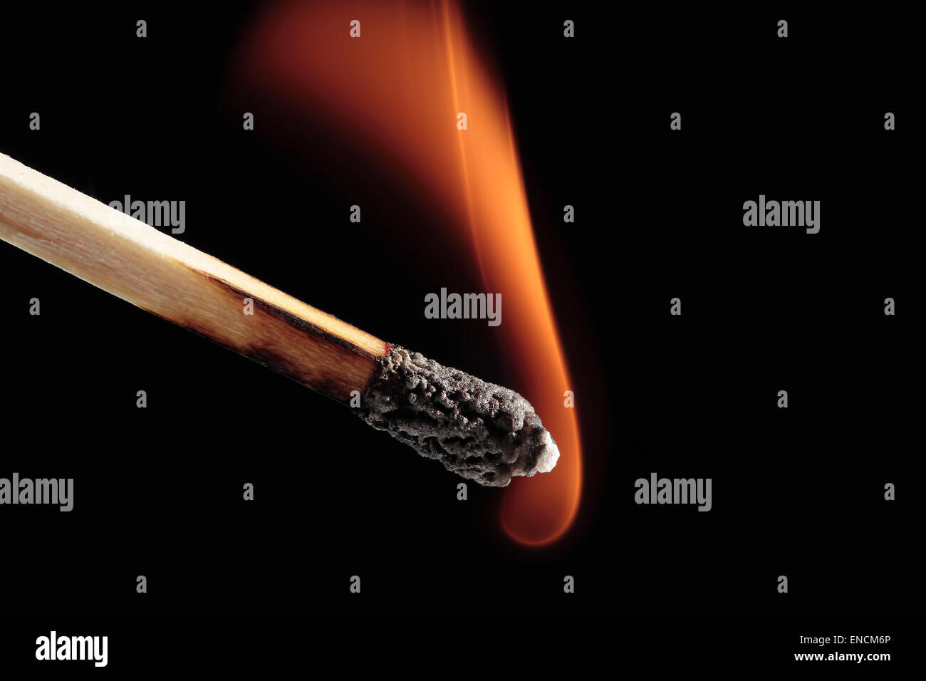 closeup of a burning matchstick on black background - Stock Image