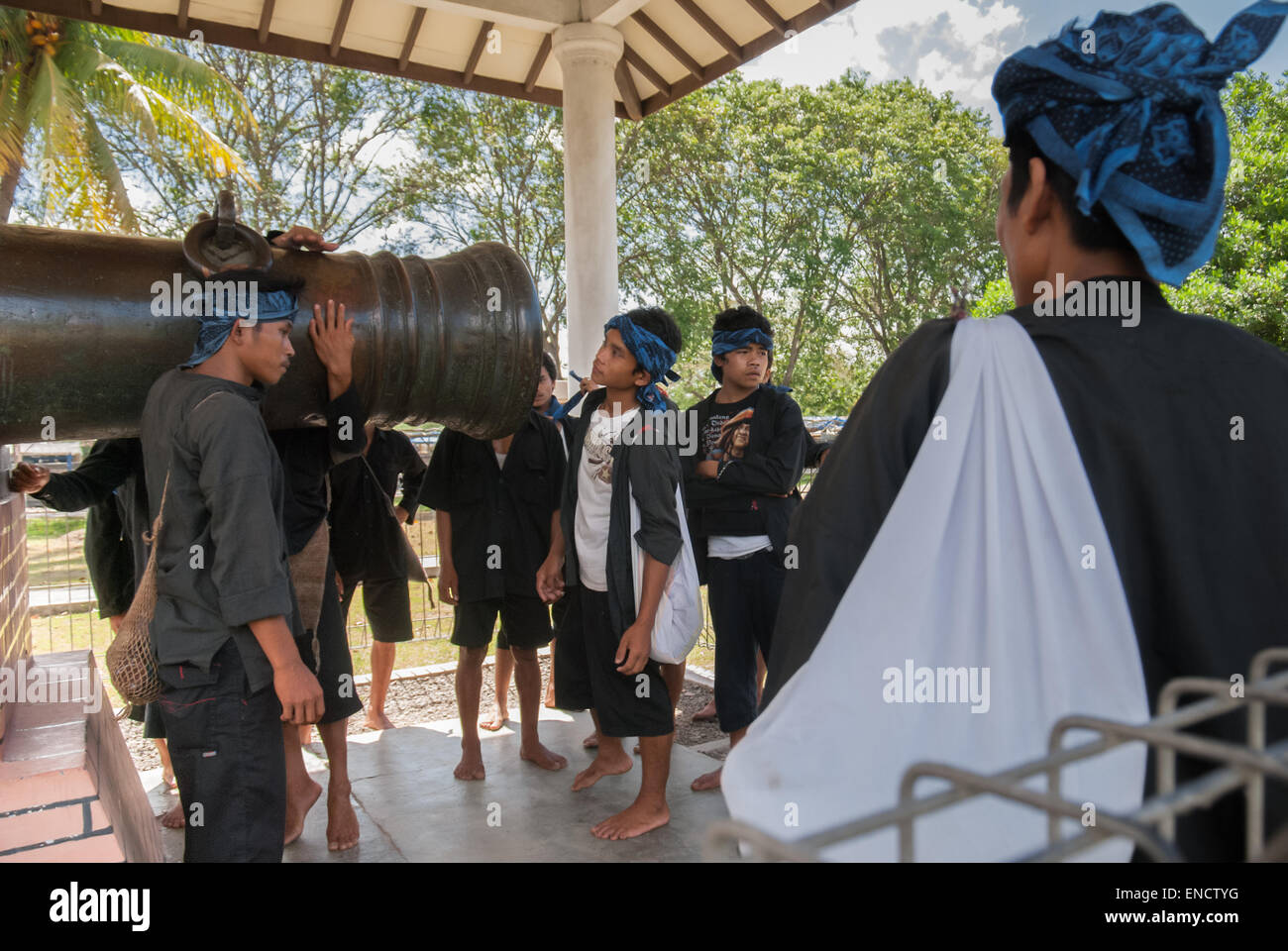 Indigenous people of Baduy tribe examines a Dutch colonial cannon as they pause during long walking journey. Banten, - Stock Image