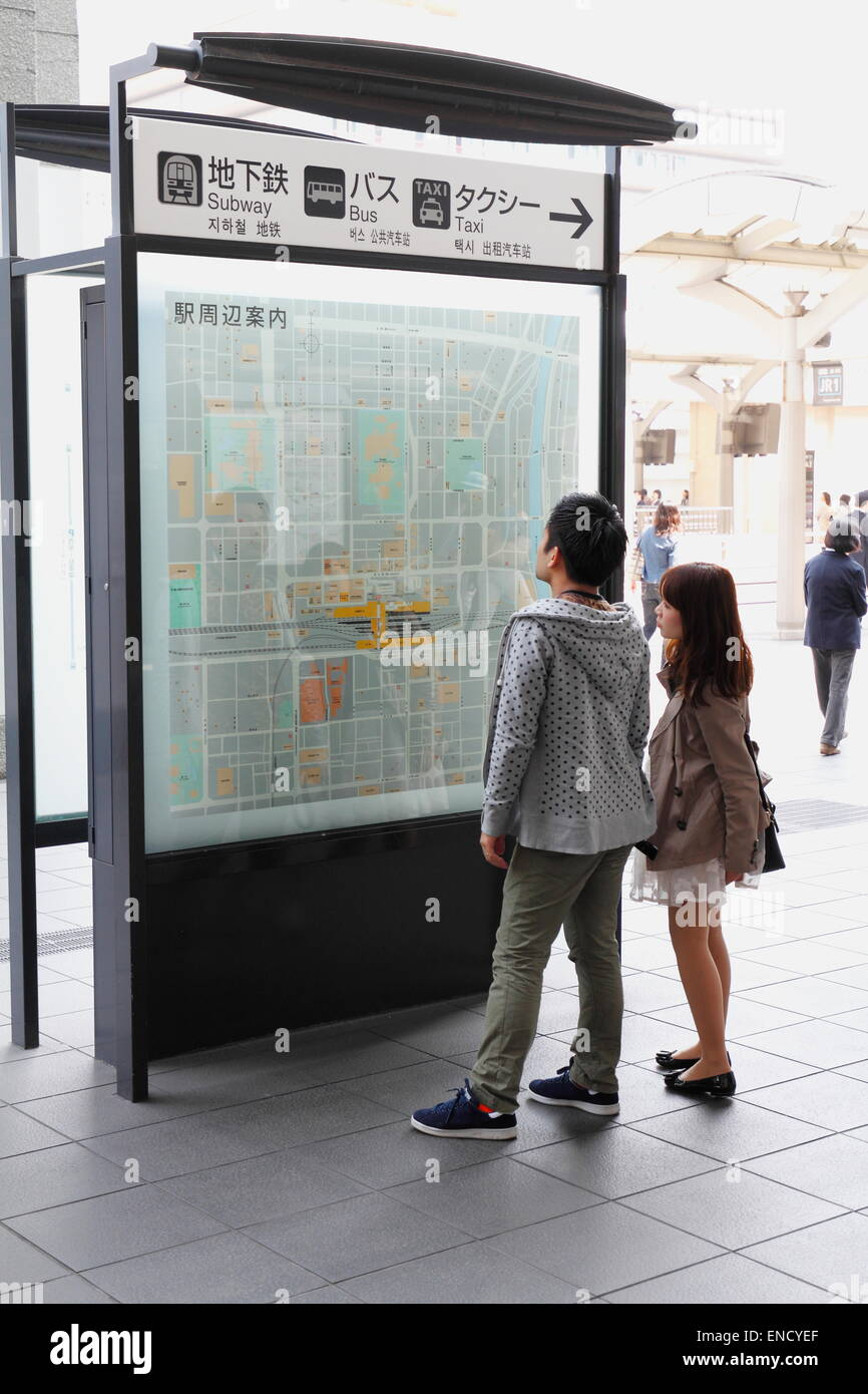 Young Asian Couple Lo Ng At The Bus Information Schedule Board Kyoto Train Station Japan