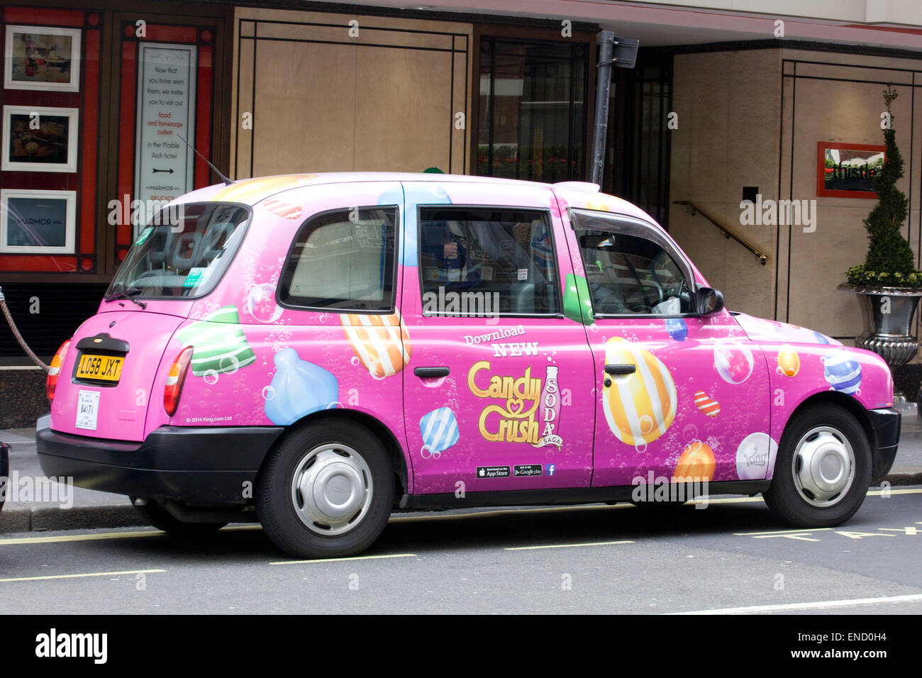 London Hackney Cab sponsored by Candy Crush in London England - Stock Image
