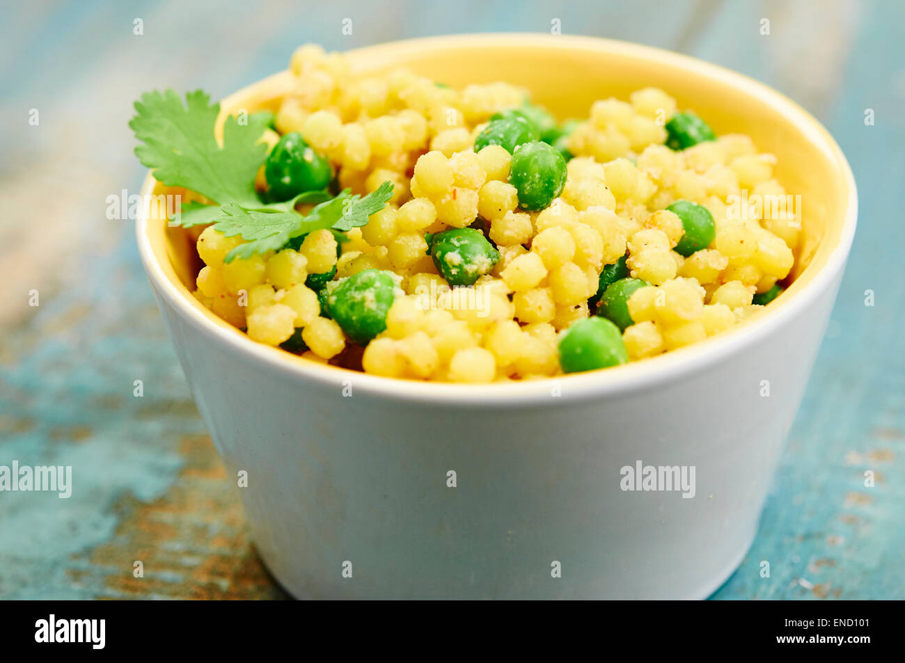 Dairy-free cheesy style salad with large round couscous and peas. - Stock Image