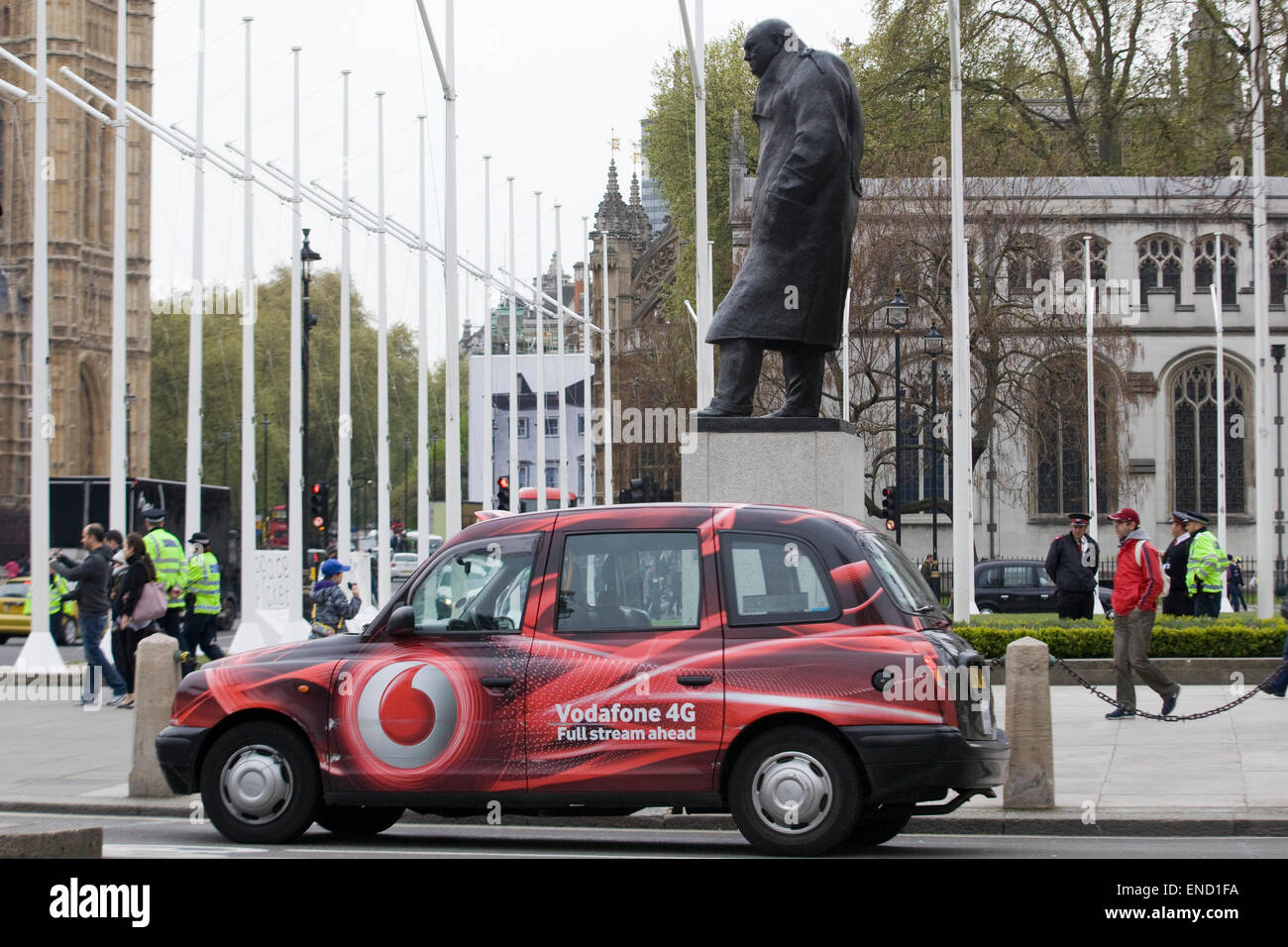 London Hackney Cab sponsored by Vodafone with the Statue of Winston Churchill in London England - Stock Image