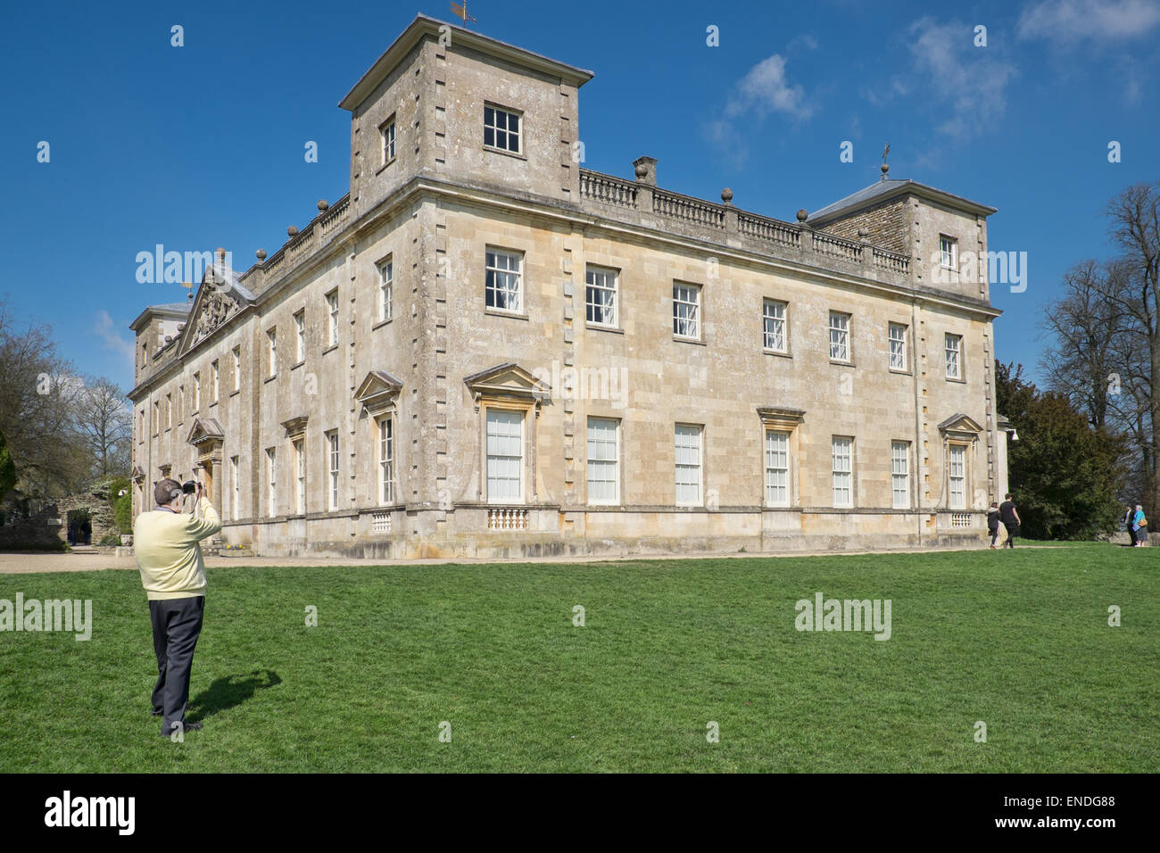A tourist taking photos of the preserved historic Palladian property, Lydiard House in Swindon, Wiltshire on a sunny - Stock Image