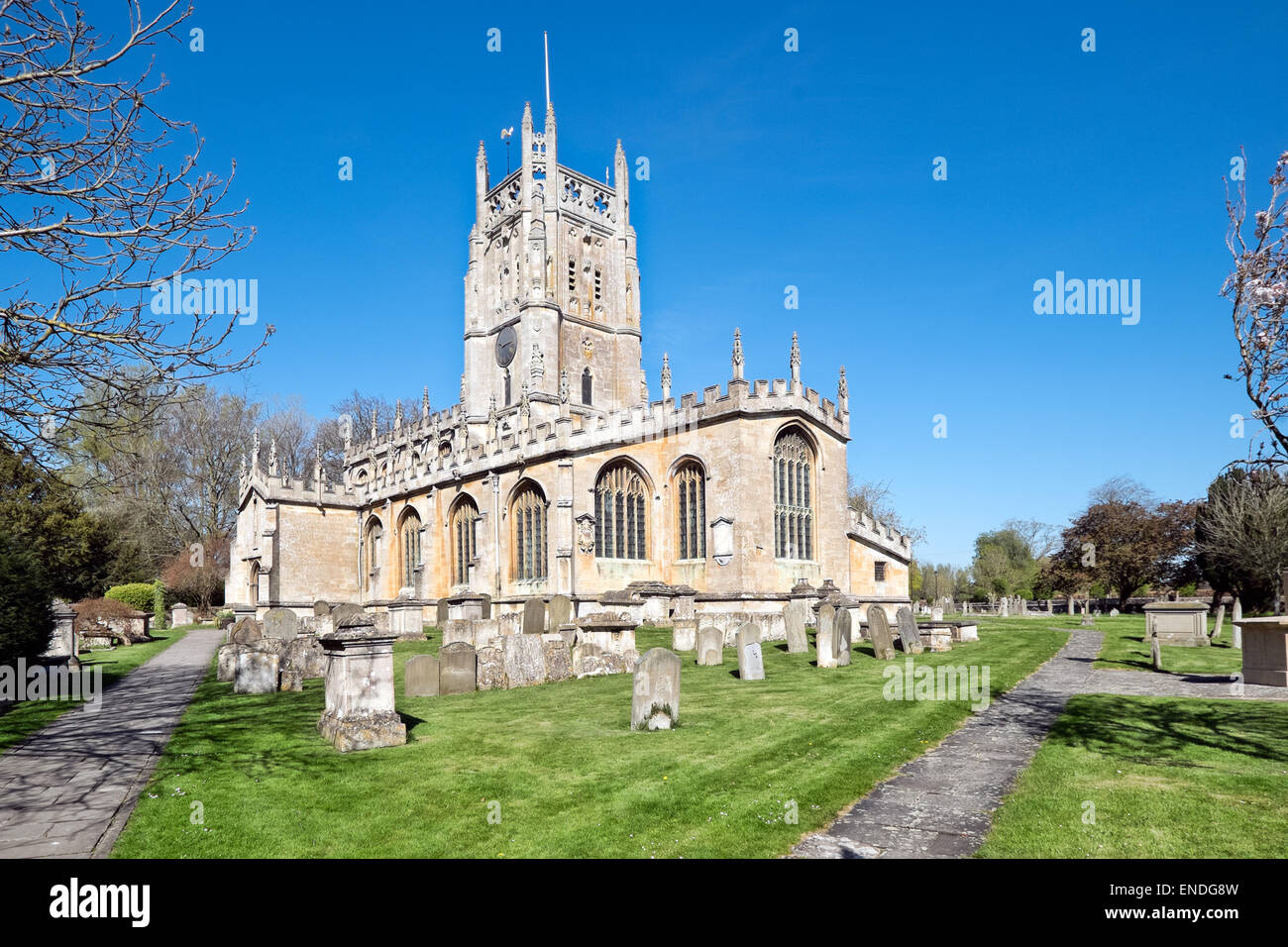 St Mary's Church & graveyard in the village of Fairford, Gloucestershire on a sunny day - Stock Image