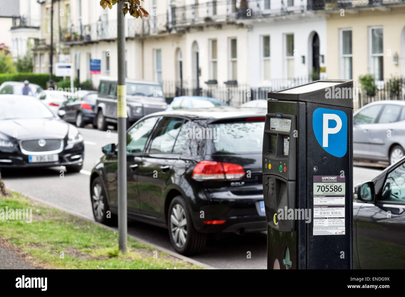 Cars parked by a meter along a parking controlled street in Cheltenham, Gloucestershire, UK - Stock Image