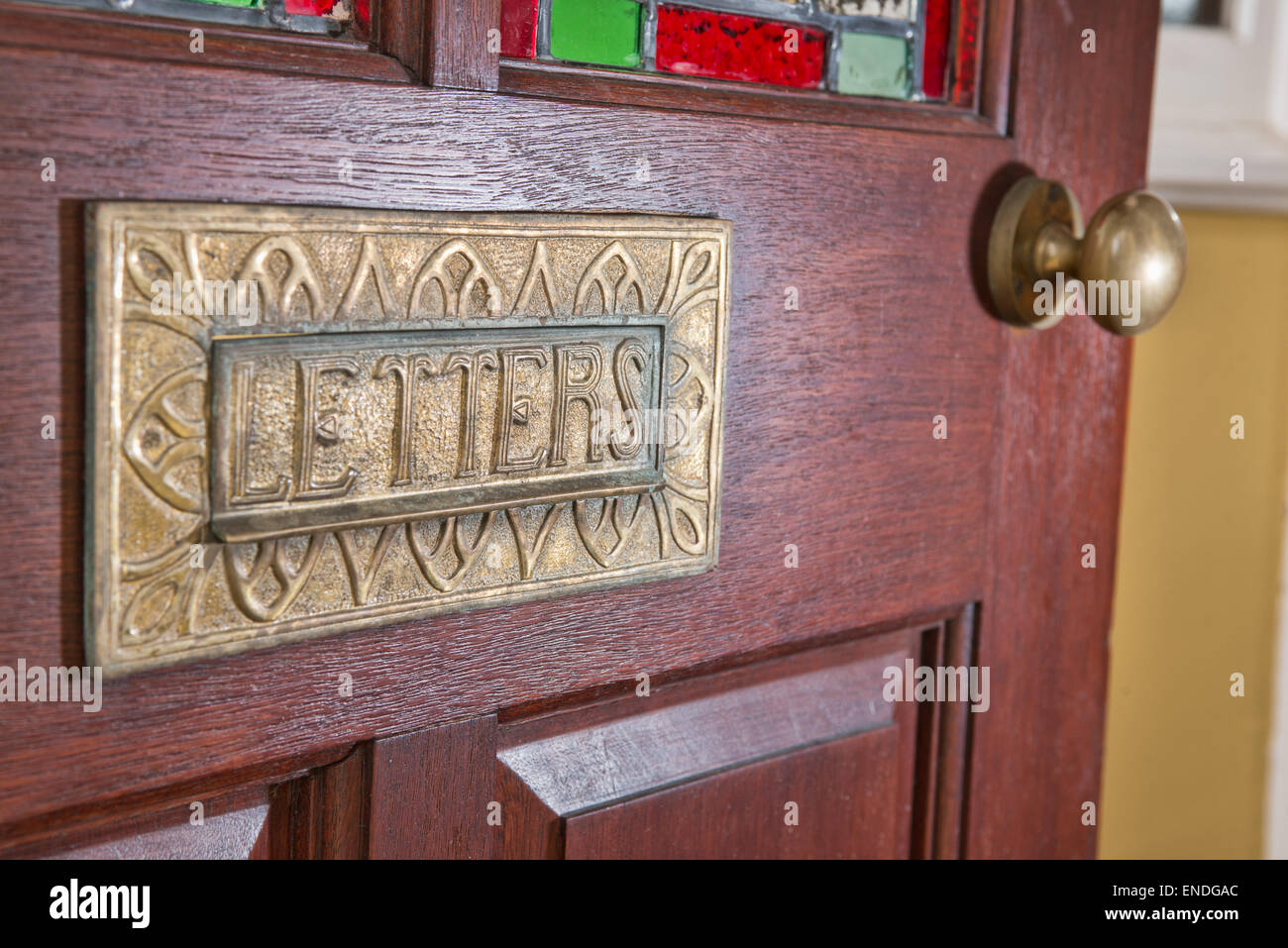 A Period letterbox with the word letters written across the flap, mounted in the front door of a home - Stock Image