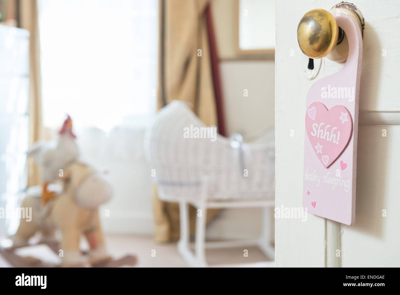 """An open door into a babies nursery bedroom,a sign hangs from a brass door knob with the motif """"shhh"""" written within Stock Photo"""